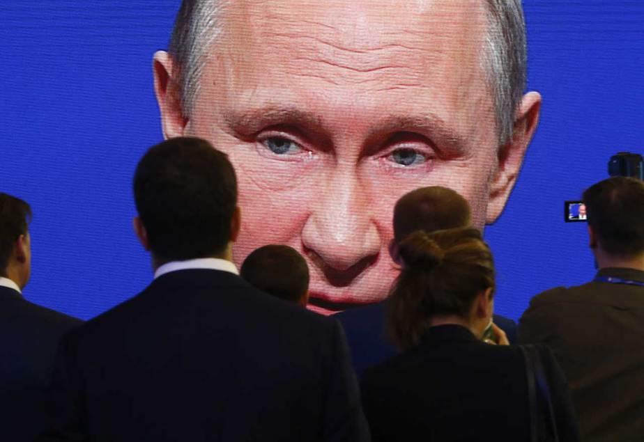 Los participantes del  Foro Económico Internacional de San Petersburgo (SPIEF) se reúnen cerca de una pantalla electrónica que muestra al presidente Vladimir Putin, quien interviene en una de las sesiones (02/06/2017) Reuters