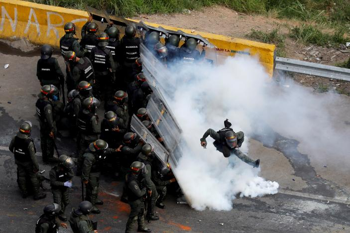 FILE PHOTO: A riot security forces member kicks a tear gas canister during protests at a march to state Ombudsman's office in Caracas, Venezuela May 29, 2017. REUTERS/Carlos Garcia Rawlins/File Photo