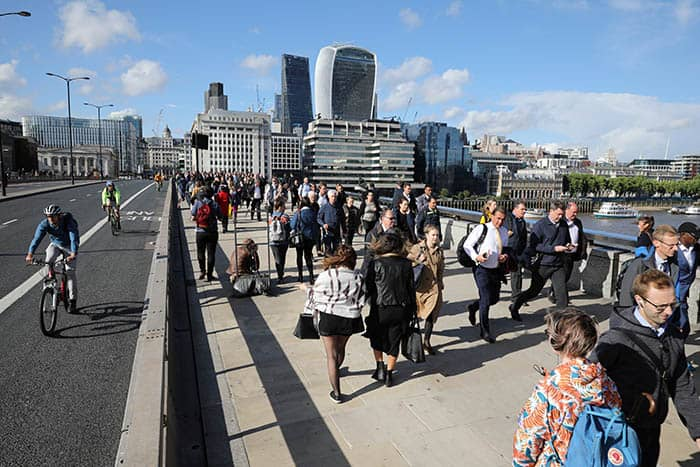 Pedestrians walk over London Bridge, past a barrier, near the recent attack on London Bridge and Borough Market,, London, Britain June 6, 2017. REUTERS/Marko Djurica - RTX39BJI