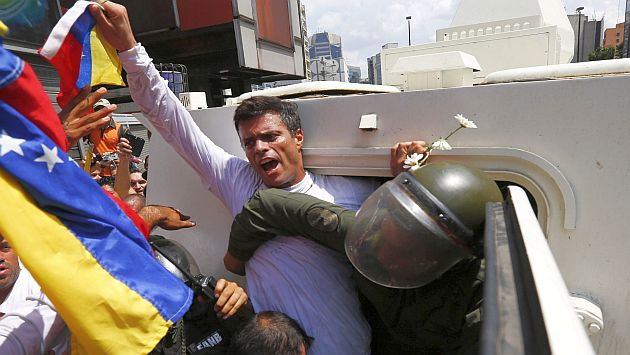 Venezuelan opposition leader Leopoldo Lopez gets into a National Guard armored vehicle in Caracas February 18, 2014. Lopez, wanted on charges of fomenting deadly violence, handed himself over to security forces on Tuesday, Reuters witnesses said. Lopez, a 42-year-old U.S.-educated economist who has spearheaded a recent wave of protests in Venezuela, got into an armored vehicle after giving a speech to an opposition rally in Caracas. REUTERS/Jorge Silva (VENEZUELA - Tags: POLITICS CIVIL UNREST TPX IMAGES OF THE DAY)