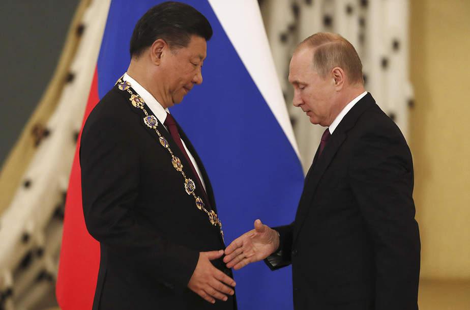 El presidente ruso Vladimir Putin (R) estrecha la mano con su homólogo chino Xi Jinping después de concederle la Orden de San Andrés Apóstol el Primero Calificado durante una reunión