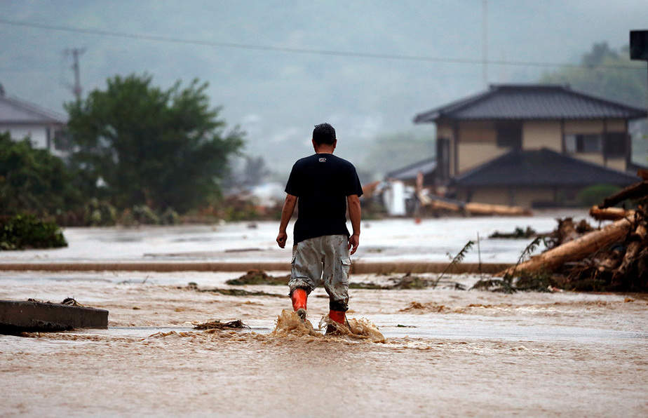 Un residente local camina en una zona dañada por un río hinchado después de una fuerte lluvia en Asakura, Prefectura de Fukuoka, Japón