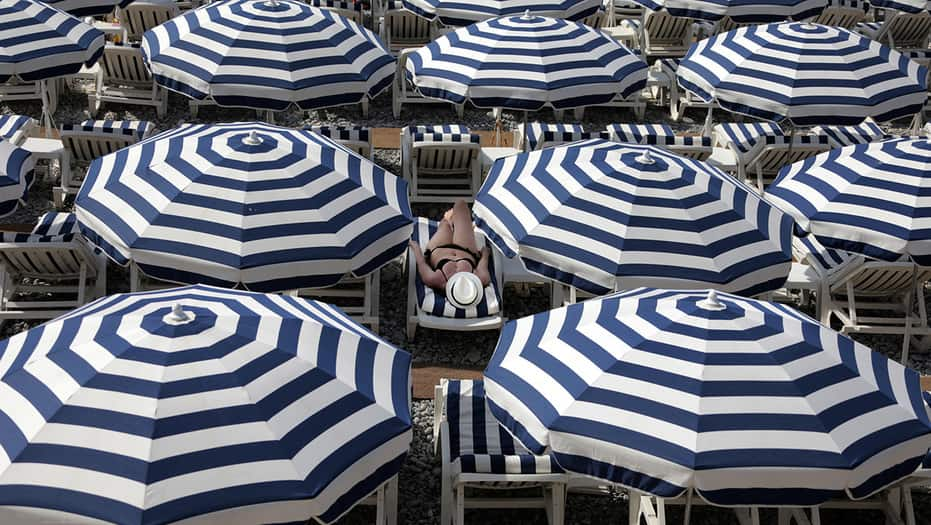 Un turista disfruta del sol en una playa cubierta con los paraguas en el Promenade des Anglais durante un día de verano asoleado en Niza, Francia, 11 de julio de 2017. REUTERS / Eric Gaillard IMAGENES TPX DEL DÍA