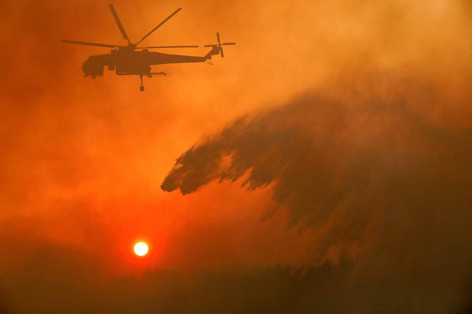 Un helicóptero de bomberos hace caer agua mientras un incendio forestal arde cerca de la aldea de Metochi, al norte de Atenas, Grecia