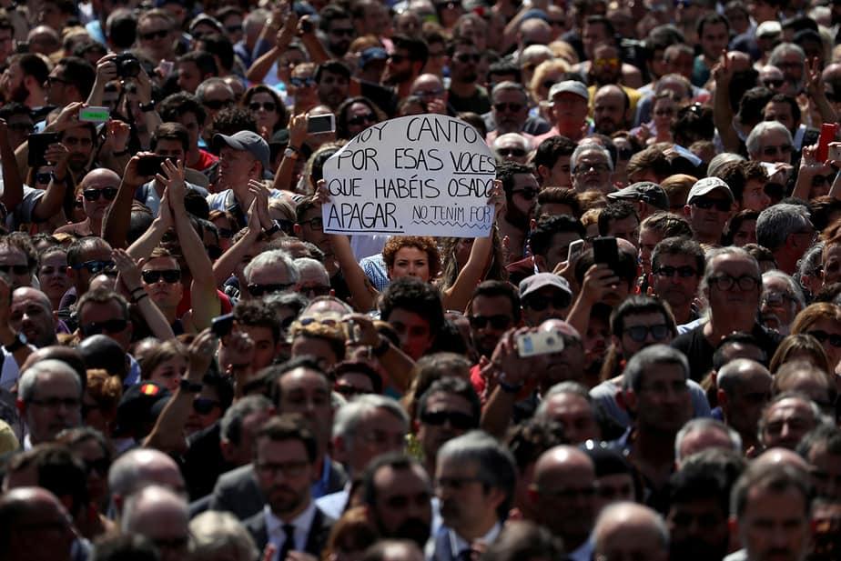 """Una mujer tiene un cartel que dice """"canto hoy por aquellas voces que te has atrevido a callar, no tememos"""", observando un minuto de silencio en la Plaça de Catalunya, un día después de que una furgoneta chocó contra peatones en Las Ramblas Barcelona"""