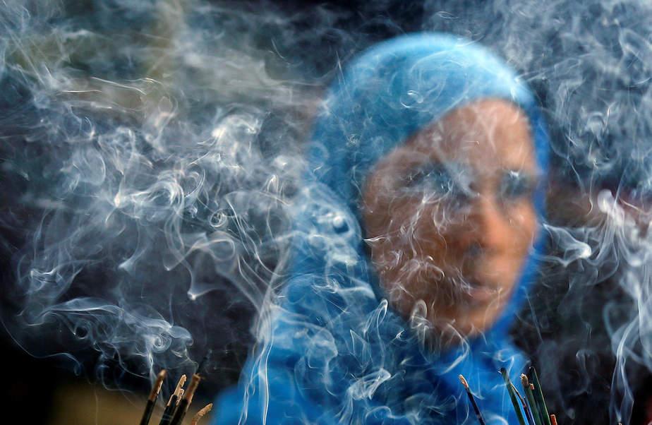 El humo se levanta de palillos del incienso de la quemadura mientras que una mujer ruega dentro del santuario del santo Nizamuddin Auliya musulmán de Nizamuddin en la India