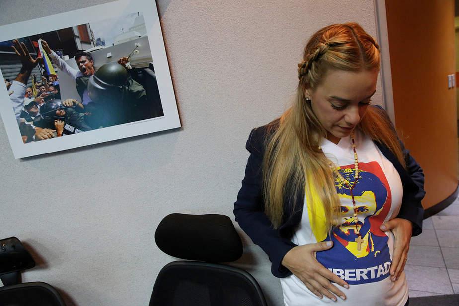 Lilian Tintori, esposa del líder opositor Leopoldo López, toca su vientre junto a una foto de su esposo, antes de una reunión con corresponsales extranjeros en Caracas, Venezuela