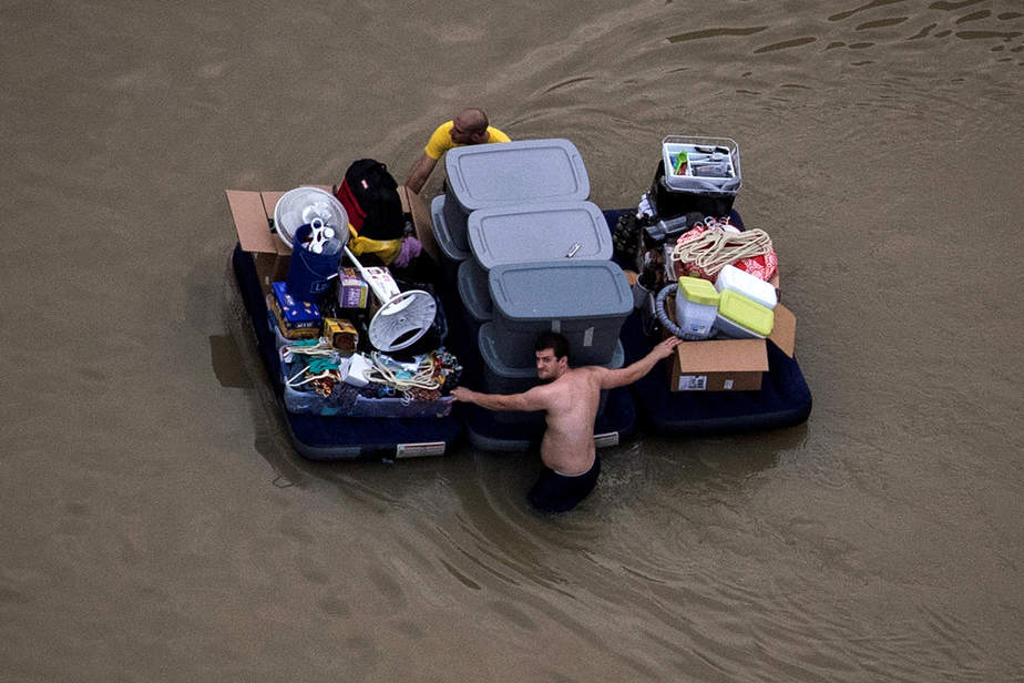 Residents wade with their belongings through flood waters brought by Tropical Storm Harvey in Northwest Houston, Texas, U.S. August 30, 2017. Picture taken August 30, 2017. REUTERS/Adrees Latif     TPX IMAGES OF THE DAY