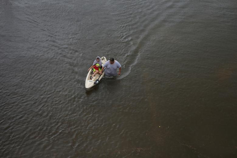 Jesús Rodríguez rescata a Gloria García después de que la lluvia inundó Pearland, en las afueras de Houston, Texas. REUTERS / Adrees Latif