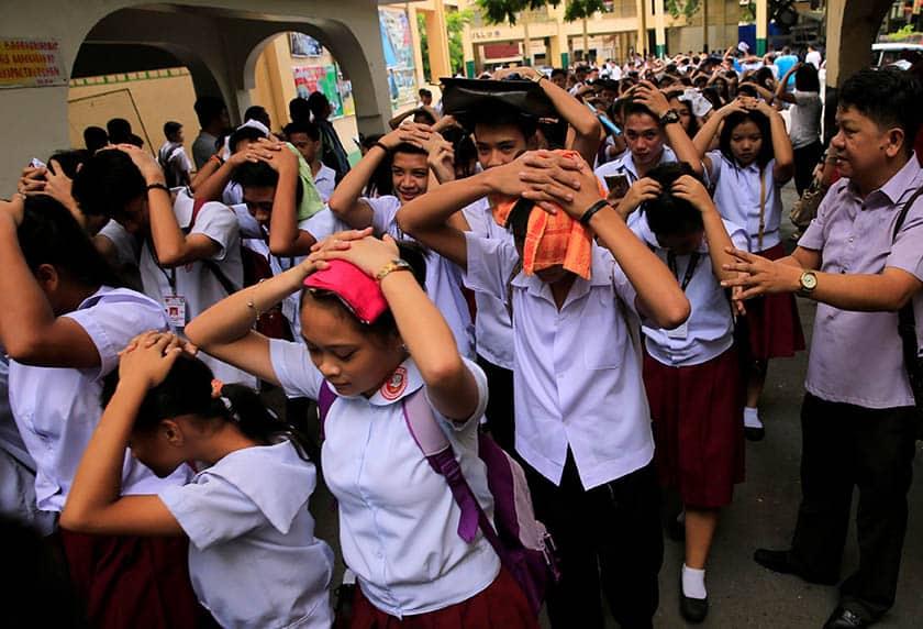 Estudiantes se protegen la cabeza ante el terremoto de Filipinas.