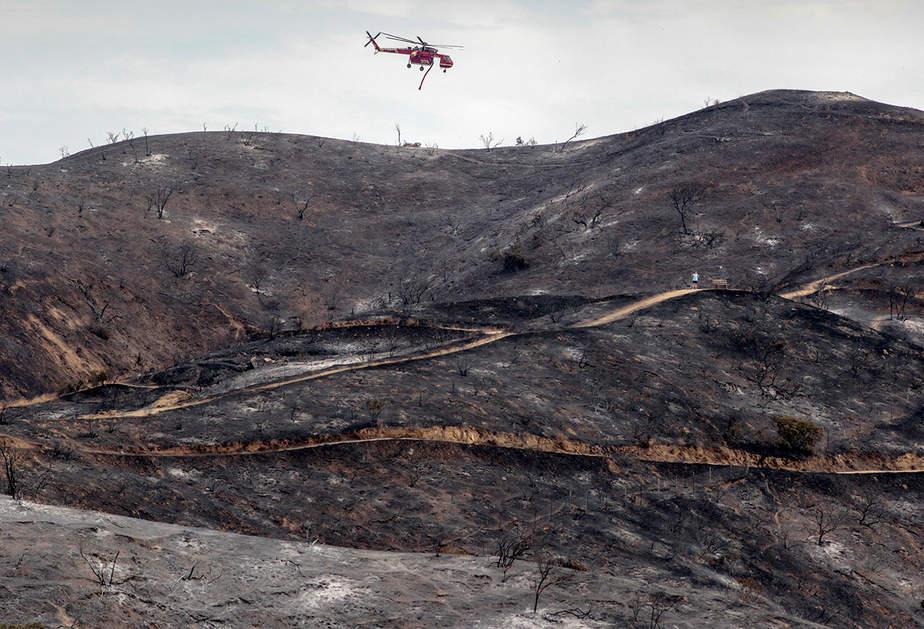 Un helicóptero de fuego vuela sobre una ladera carbonizada durante el incendio de La Tuna Canyon sobre Burbank, California