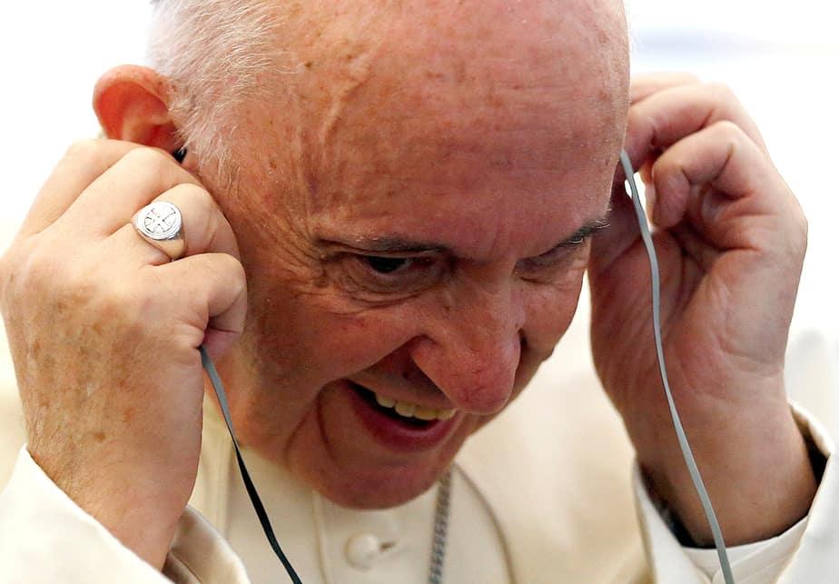 El Papa Francis escucha un mensaje del teléfono móvil de un periodista mientras está a bordo de su avión que está enlazado a Bogotá, Colombia
