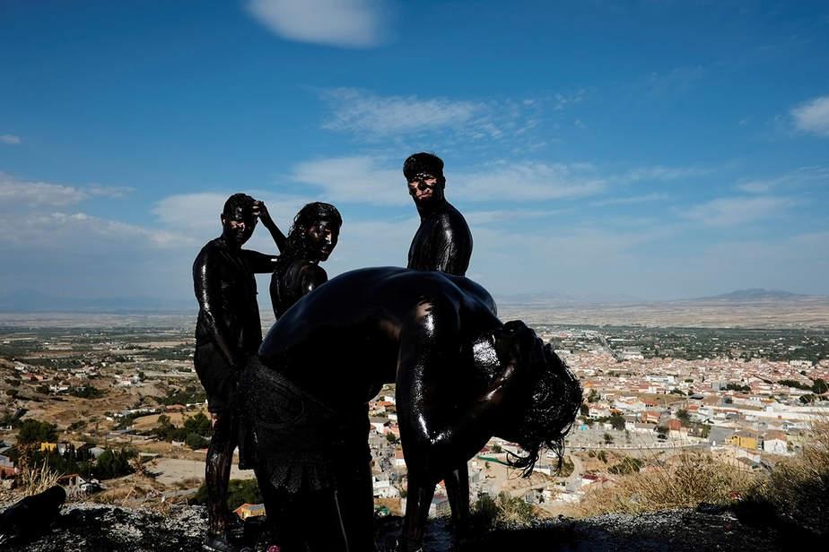 """Un festejante pone grasa en su cuerpo mientras participa en el festival anual de Cascamorras en Baza, sur de España el 6 de septiembre de 2017. El festival fue inspirado por una disputa entre la ciudad de Baza y Guadix sobre la posesión de un icono de la Virgen de Piedad. Los Cascamorras se refieren a representantes de Guadix, que fueron enviados a Baza para recuperar la estatua. Como los Cascamorras tuvieron que quedarse perfectamente limpios para ganar posesión de la estatua, los residentes de Baza intentan hacerlos tan """"sucios"""" como sea posible."""