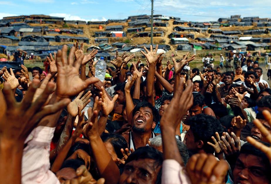 Los refugiados de Rohingya se estiran las manos para recibir ayuda distribuida por organizaciones locales en el campamento improvisado de Balukhali en Cox's Bazar, Bangladesh