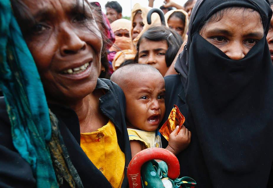 Un bebé refugiado rohingya llora mientras su madre se apresura a pedir ayuda en Cox's Bazar, Bangladesh