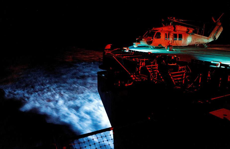Un helicóptero de la Armada MH-60S Seahawk está iluminado por las luces de la cubierta, mientras que el USS Kearsarge en la popa está iluminado por las luces azules de arrastre como los motores del buque a la velocidad máxima hacia las islas afectadas por el huracán María, en el Mar Caribe