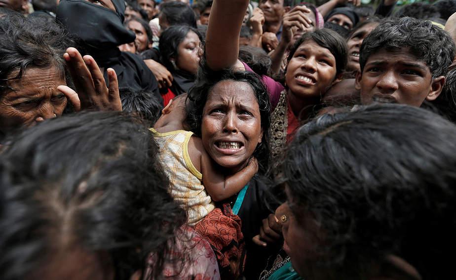 Una mujer reacciona mientras los refugiados rohingyas esperan para recibir ayuda en Cox's Bazar, Bangladesh