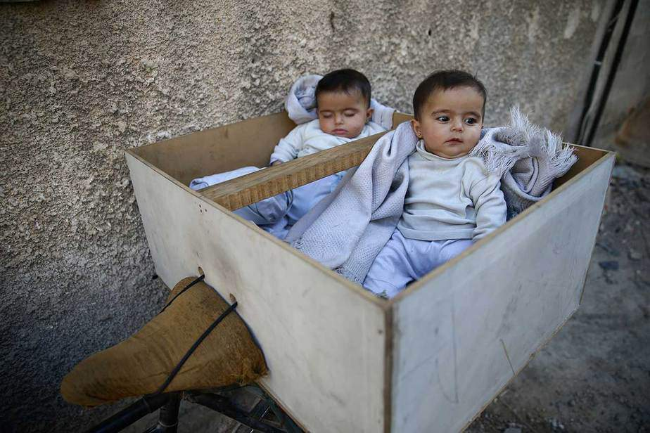 """Los mellizos de cinco meses Farah y Marah esperan que sus padres reciban distribuciones de leche de un centro médico en el área de Hamoria, en Ghouta, Siria. Los suministros apenas han ingresado en meses. La escasez ha hecho subir los precios aún más. Los residentes y los trabajadores locales de ayuda dicen que temen lo peor si nada cambia cuando llega el frío y se agotan las existencias. A través de una serie de ofensivas y acuerdos de evacuación, el gobierno de Damasco ha derrotado a los bolsillos de la oposición en torno a la capital. Eastern Ghouta se ha resistido, pero los residentes dicen que ahora se habla por primera vez de aceptar evacuar. """"Las personas están bajo presión, van a entrar en erupción. No hay leche para bebés. Madres y padres están viendo a sus hijos pasar hambre. Quieren una solución de cualquier manera, a cualquier precio"""", dijo Adnan, de 30 años, quien dirige un local grupo de ayuda. REUTERS / Bassam Khabieh"""
