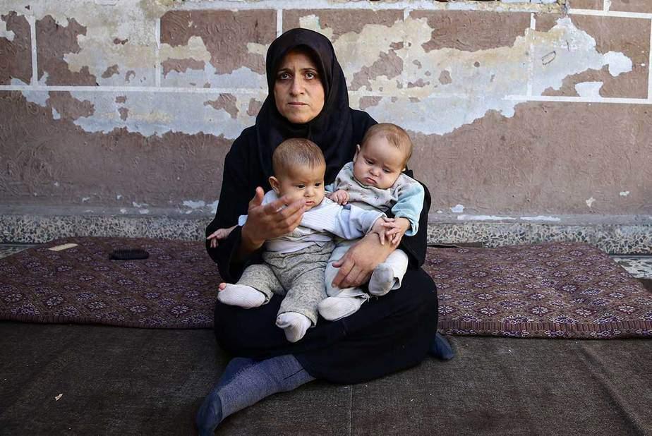 """Um Said, madre de seis hijos, dice que está demasiado hambrienta para amamantar a sus gemelas de seis meses, Marwa y Safa. """"Puse al niño sobre el pecho, pero no hay leche. No estoy comiendo. Me dormí sin cenar anoche"""", dijo. """"A veces me golpeo contra la pared"""", dijo. """"Por el amor de Dios, abre el camino. En nombre del profeta, te beso las manos y los pies, abre el camino para nosotros. Vamos a morir de hambre. Estamos comiendo de los contenedores de basura"""". REUTERS / Bassam Khabieh"""