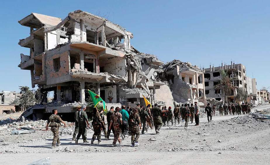 Los combatientes del SDF desfilan edificios destruidos mientras celebran la victoria y la liberación de Raqqa de los militantes del Estado Islámico, en Raqqa, Siria, el 17 de octubre. (Reuters / Erik De Castro)