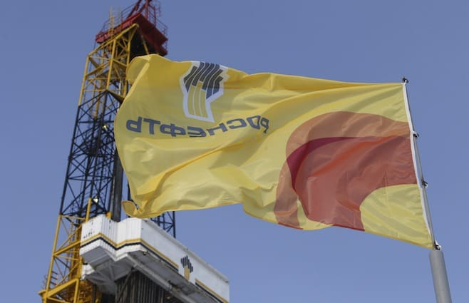 A flag with the logo of Rosneft company flies next to an oil derrick at Suzunskoye oil field north from Krasnoyarsk, Russia, in this March 26, 2015 file photo. Russian state oil producer Rosneft ROSN.MM will be forced to postpone drilling a second well in the Kara Sea for at least two more years, three sources told Reuters, as a result of Western sanctions over the Ukraine crisis. To match Exclusive RUSSIA-ROSNEFT/KARA-SEA   REUTERS/Sergei Karpukhin/Files