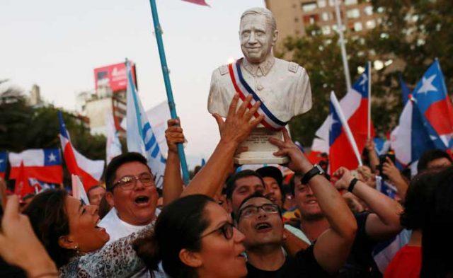 Los partidarios del candidato presidencial electo Sebastián Piñera celebran con un busto del ex dictador chileno Augusto Pinochet después de escuchar los resultados de las elecciones presidenciales en Santiago (Reuters)