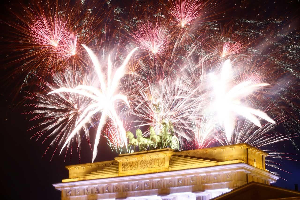 Fuegos artificiales iluminan escultura de la cuadriga en lo alto de la puerta de Brandenburgo en Berlin. REUTERS
