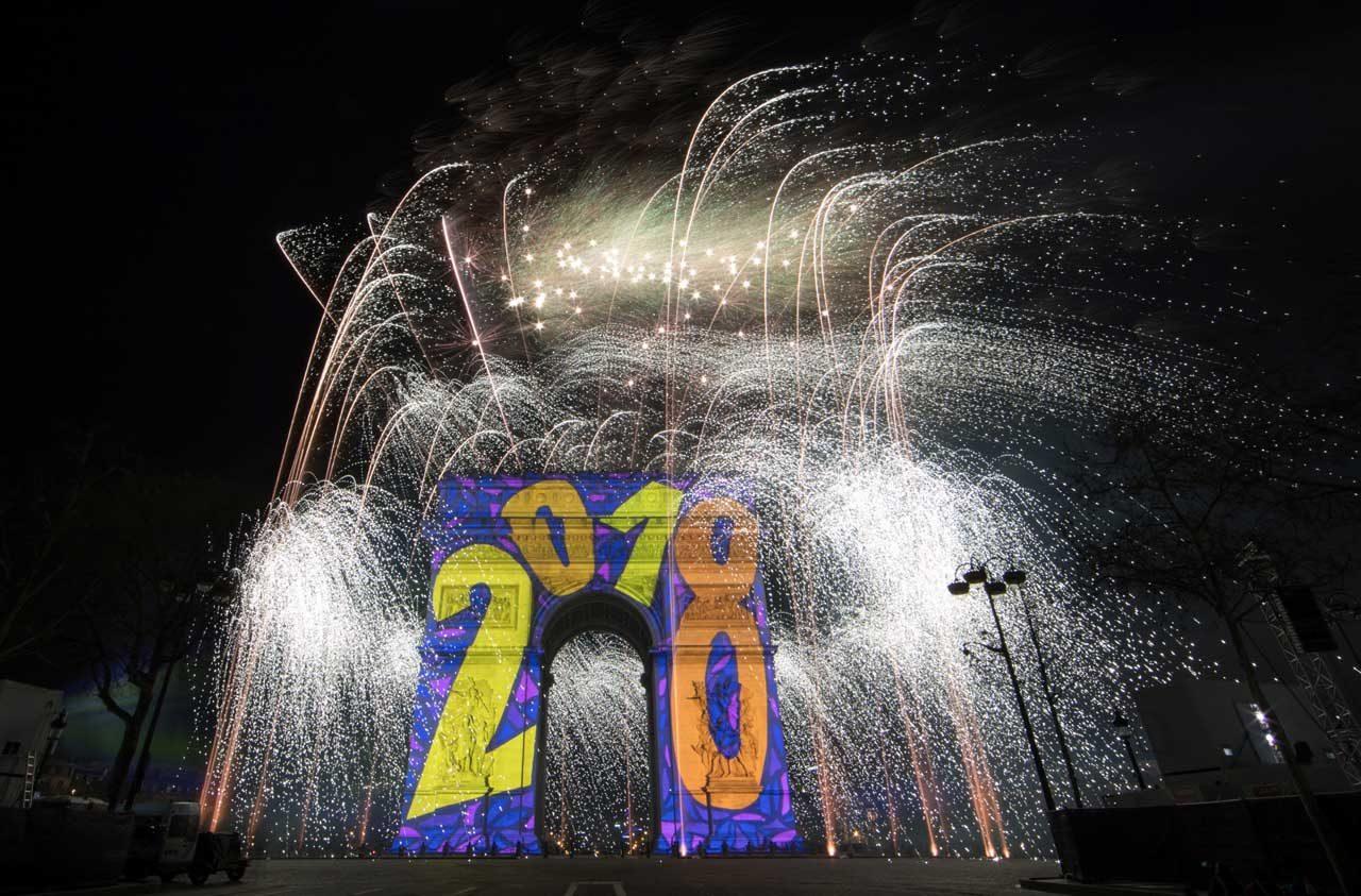 Los fuegos artificiales iluminan el cielo sobre el Arco del Triunfo en la avenida de los Campos Elíseos en París mientras los juerguistas participan en las celebraciones del Año Nuevo, a principios del 1 de enero de 2018. REUTERS