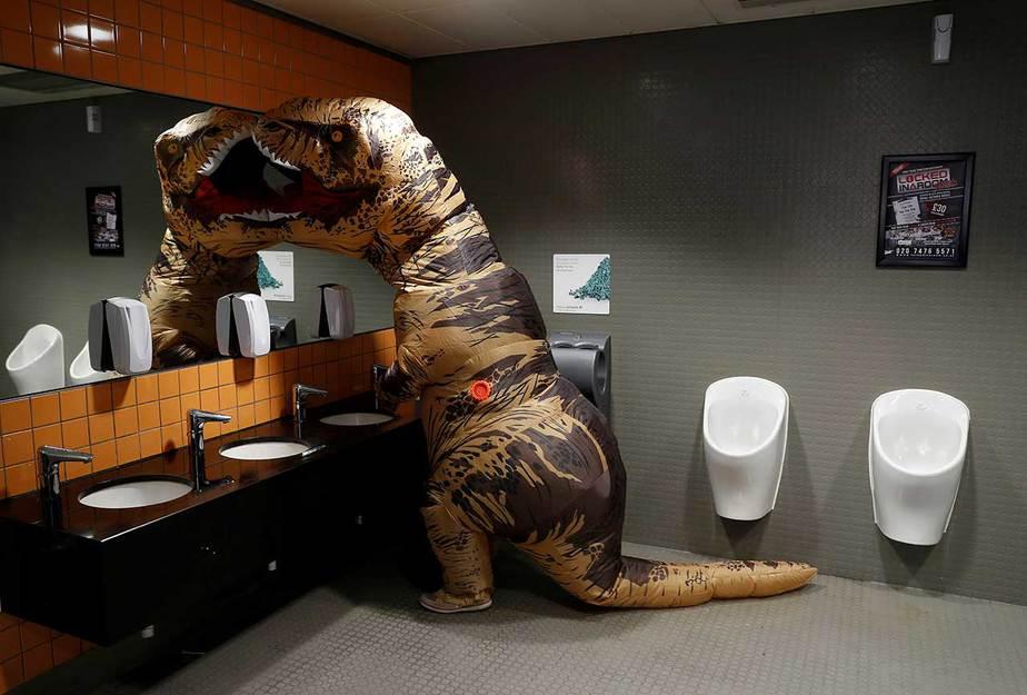 Un visitante vestido con un traje de T. rex utiliza el lavabo en el London Comic Con, en el centro de exposiciones ExCel en el este de Londres, Gran Bretaña 27 de octubre de 2017. REUTERS / Peter Nicholls