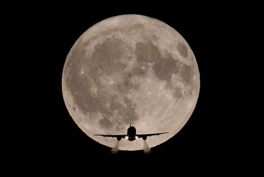Un avión de pasajeros, con una luna de cosecha completa vista atrás, realiza su aproximación final de aterrizaje hacia el aeropuerto de Heathrow en Londres, Gran Bretaña, el 5 de octubre de 2017. REUTERS / Toby Melville