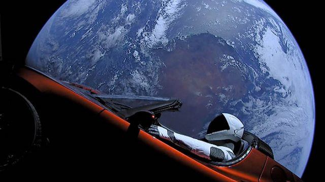A cherry red Tesla Roadster automobile floats through space after it was carried there by SpaceX's Falcon Heavy