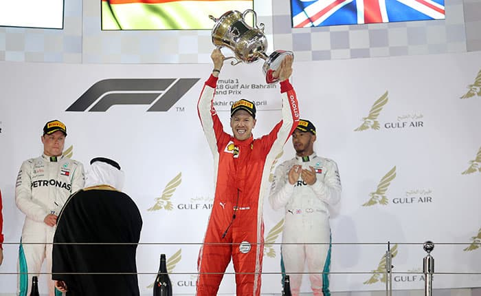 Formula 1 F1 - Bahrain Grand Prix - Bahrain International Circuit, Sakhir, Bahrain - April 8, 2018   Ferrari's Sebastian Vettel celebrates with the trophy after winning the race as Mercedes' Valtteri Bottas and Mercedes' Lewis Hamilton look on   REUTERS/Hamad I Mohammed