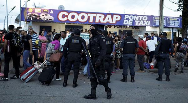Policías antidisturbios conversan con venezolanos después de revisar sus pasaportes o documentos de identificación en el punto de control Pacaraima, estado de Roraima, en Brasil (Reuters)