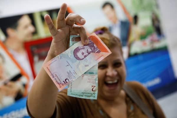 Una mujer sonríe mientras muestra los nuevos dos y cinco billetes de Bolívar Soberano, después de que los retiró de un cajero automático  en una sucursal del banco Mercantil en Caracas