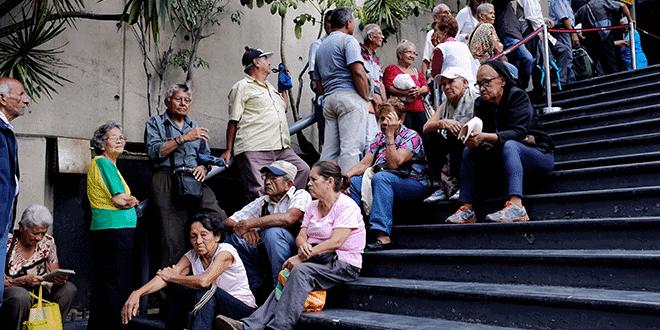 En la imagen, una grupo de personas aguarda su turno en un banco de Caracas para cobrar su pensión el 14 de septiembre de 2018. REUTERS/Marco Bello