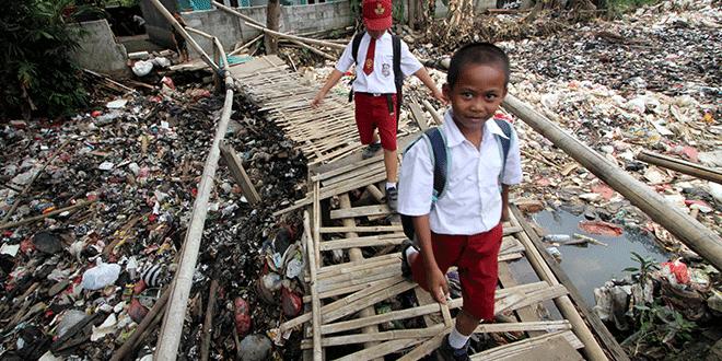 Estudiantes cruzan al puente de bambú, sobre un arroyo lleno de basura que se ramifica en el río Ciliwung, en Bogor, Indonesia, el 25 de septiembre de 2018. Fotografía tomada el 25 de septiembre de 2018. Antara Photo / Yulius Satria Wijaya a través de REUTERS
