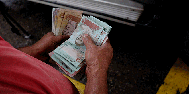 Un trabajador de una gasolinera de PDVSA cuenta bolívares en Caracas, sep 24, 2018. REUTERS/Marco Bello