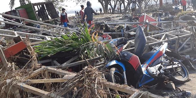 Varias personas pasean entre las ruinas de un puesto en la playa después de que el tsunami pasase por Palu, en la isla indonesia de Sulawesi el 29 de septiembre/Reuters