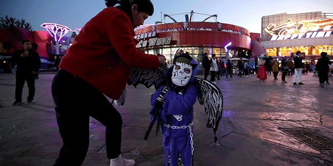 Una madre ayuda a su hijo con el disfraz antes de un evento de Halloween en el parque Happy Valley en Beijing, China, 31 de octubre de 2018. REUTERS / Jason Lee
