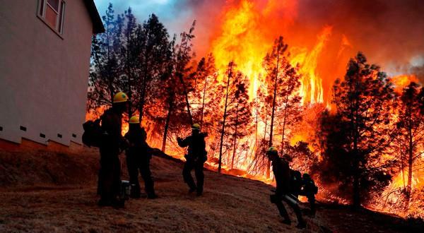 Grupo de bomberos combaten las llamas para intentar salvar un hogar en Paradise, California. REUTERS/Stephen Lam