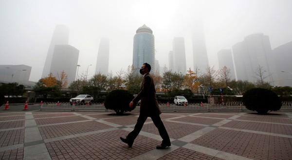 Un hombre camina con una mascarilla por el distrito empresarial del centro de Beijing, China, el 14 de noviembre de 2018. REUTERS/Jason Lee