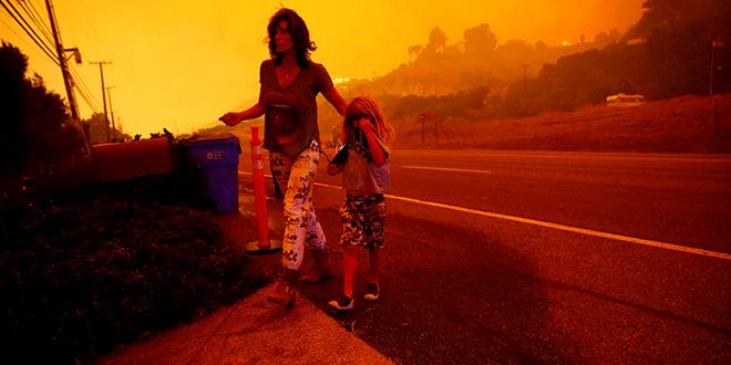 Gabi y Jonah Frank caminan por la autopista de la costa del Pacífico mientras el incendio de Woolsey amenaza su hogar en Malibu, California, el 9 de noviembre de 2018. REUTERS / Eric Thayer