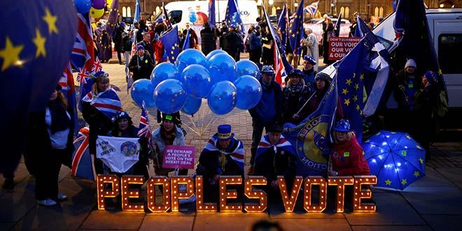 Manifestantes contra el Brexit  junto a un cartel iluminado en el entorno del Parlamento en Londres, Reino Unido, 10 de diciembre de 2018. REUTERS / Henry Nicholls