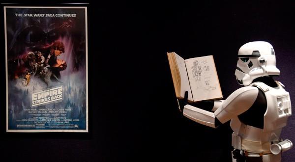"""Un hombre vestido con un traje de soldado imperial se para frente a un póster de la secuela de Star Wars """"The Empire Strikes Back"""" que pertenece al diseñador de vestuario John Mollo, durante una sesión fotográfica antes de una subasta en Bonhams en el centro de Londres, Reino Unido, 6 de diciembre del 2018. REUTERS/Toby Melville"""