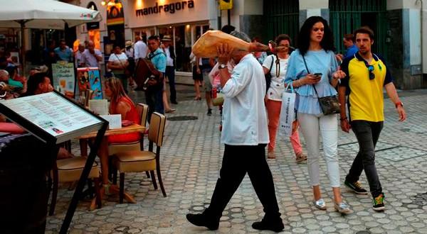 Un camarero lleva un jamón en una terraza de un resturante en el centro de Málaga, el 7 de junio de 2018. REUTERS/Jon Nazca
