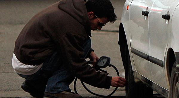 Un hombre infla un neumático. El IPC español sigue moderándose ante la baja de precios de los carburantes / REUTERS/Jon Nazca