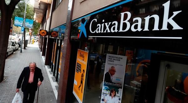 En la imagen de archivo, un hombre camina junto a una sucursal de Caixabank en Barcelona, España. REUTERS/Yves Herman
