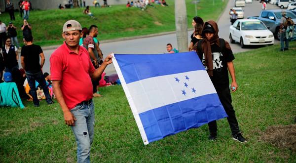 Personas sostienen una bandera de Honduras mientras esperan salir con una nueva caravana de migrantes, que se dirigirá a Estados Unidos, en una estación de autobuses en San Pedro Sula, Honduras, 14 de enero del 2019. REUTERS/Jorge Cabrera
