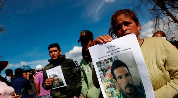 Imagen de habitantes de la zona con fotos de los desaparecidos en el lugar de la explosión, en el municipio de Tlahuelilpan, Estado de Hidalgo, en México el 19 de enero de 2019. REUTERS/Henry Romero