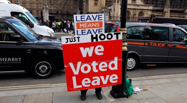 """Un manifestante a favor del Brexit muestra una pancarta en la que se puede leer """"Votamos salir"""" en las afueras del parlamento británico en Westminster."""